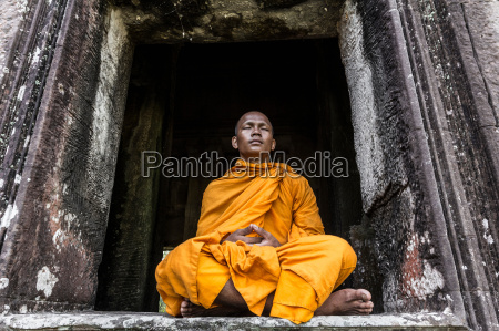 young buddhist monk meditating in temple