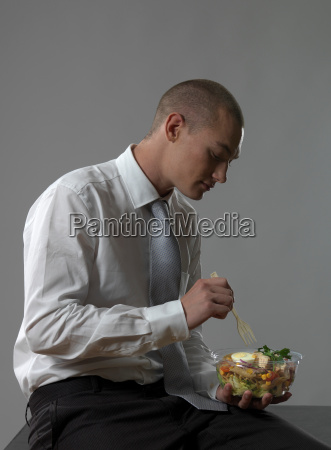 business man eating salad