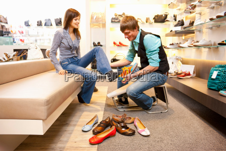 employee helping girl to fit shoes