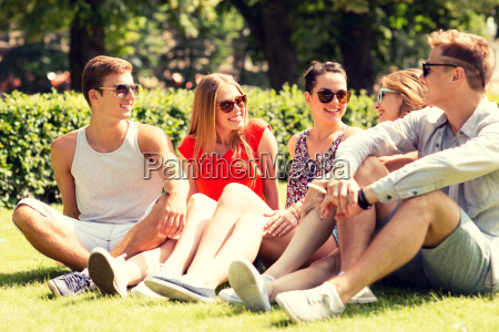 group of smiling friends outdoors sitting