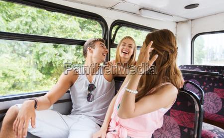 happy teenage friends traveling by bus