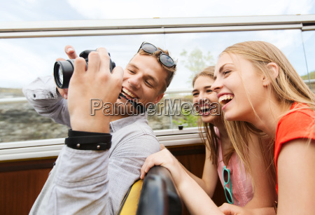 happy friends with camera traveling by