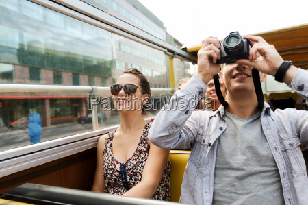 smiling couple with camera traveling by