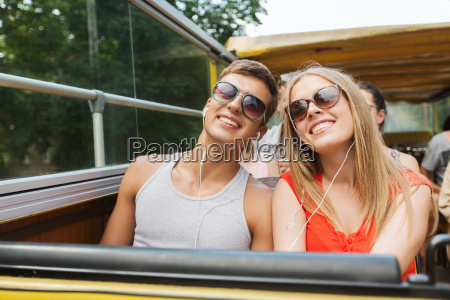 happy teenage couple traveling by tour
