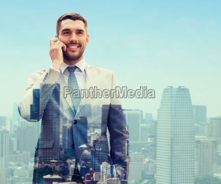 smiling businessman with smartphone in city