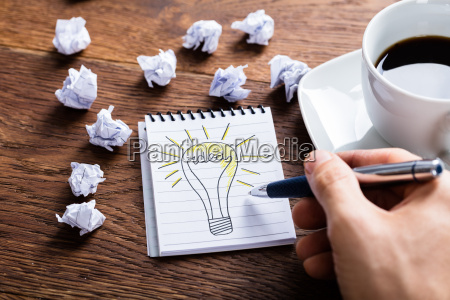 person drawing lighting bulb on notepad
