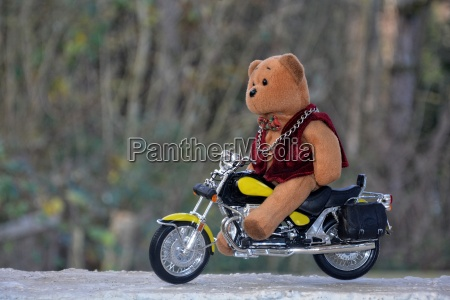 teddy bear sits on motorcycle outdoors