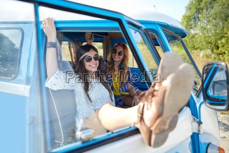 smiling young hippie women resting minivan