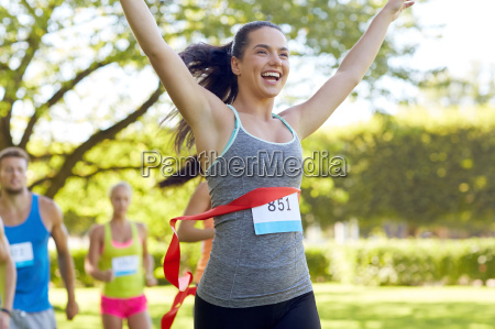happy young female runner winning on