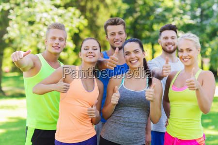 group of happy sporty friends showing