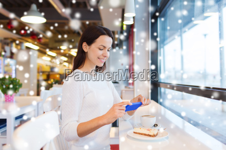 smiling woman with smartphone and coffee