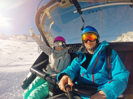 happy couple taking selfie in chairlift