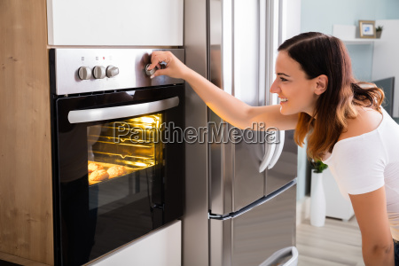 woman using microwave oven in kitchen