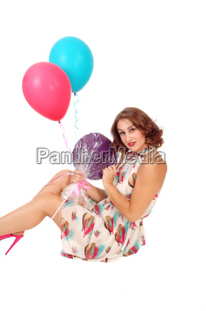 woman sitting on floor with balloons
