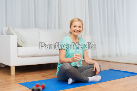 happy woman drinking water and exercising