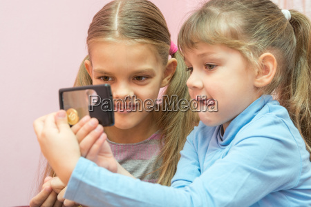 two children considered a coin through