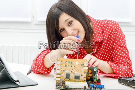 brunette woman technician repairs a computer