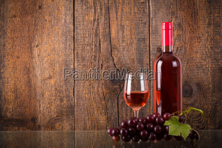 glass of rose wine with grapes