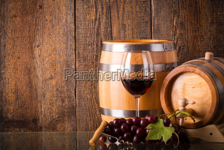 glass of red wine with barrels