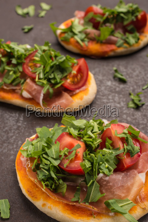 pizza with arugula tomato and ham