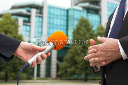 reporter holding microphone interviewing businessman or