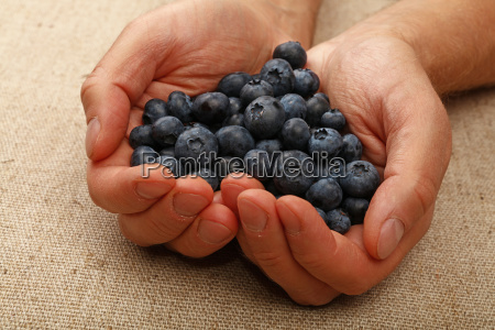 man hands with heart shaped blueberries