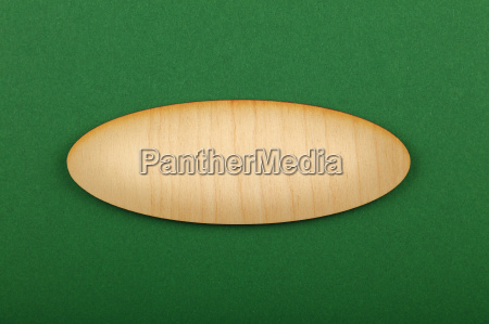 ellipse shaped wooden sign on green