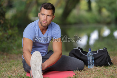handsome young man stretching at the