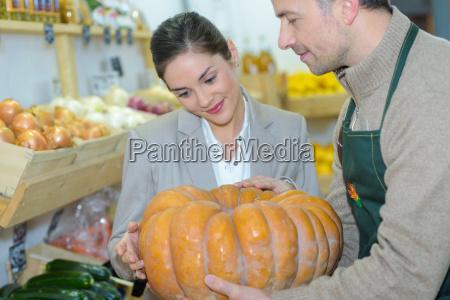 grocer showing pumpkin to customer