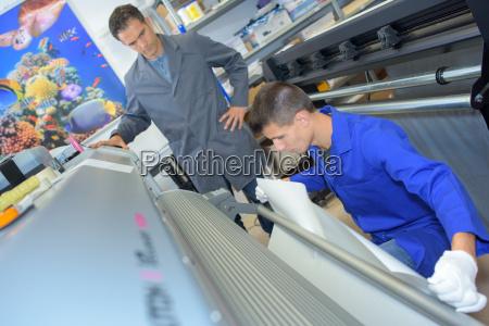 student manipulating printer under the teachers