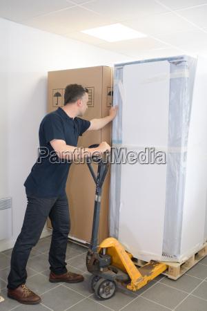 mature man moving huge cartons with