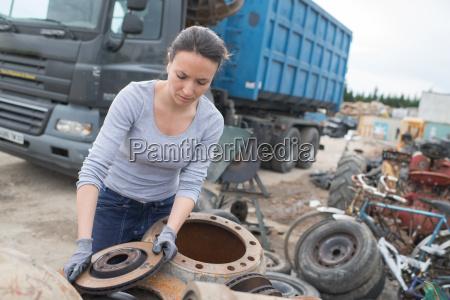 woman mechanic picking axle in car
