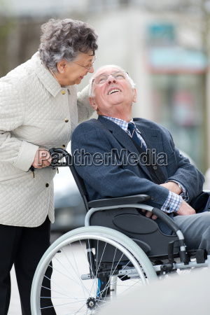 senior man with woman in wheelchair