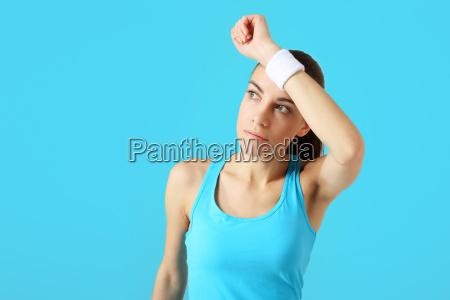 beautiful sportswoman wipes the sweat from