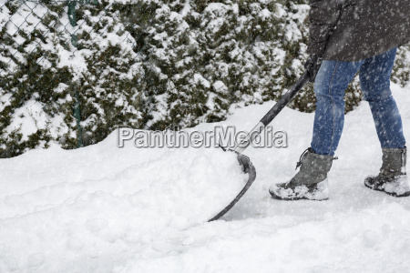 woman clearing on sidewalk while snowing