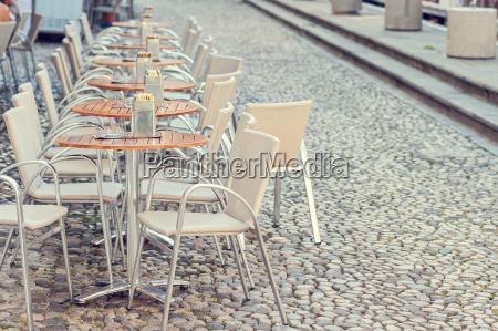 row of little tables with chairs