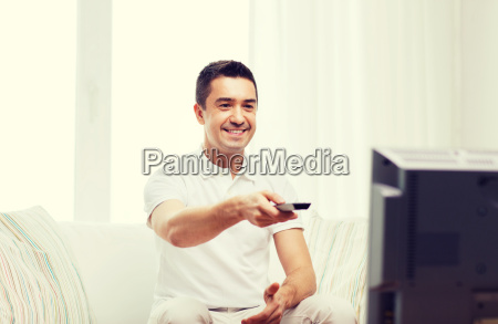 smiling man with remote control watching