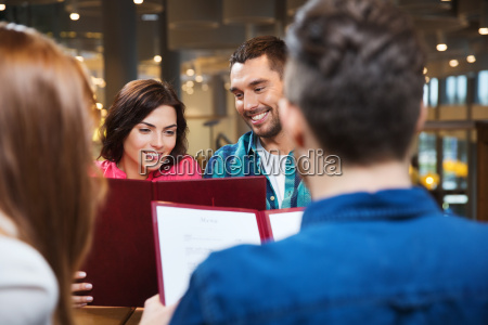 smiling couple with friends and menu