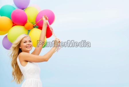 laecheln frau mit bunten luftballons draussen