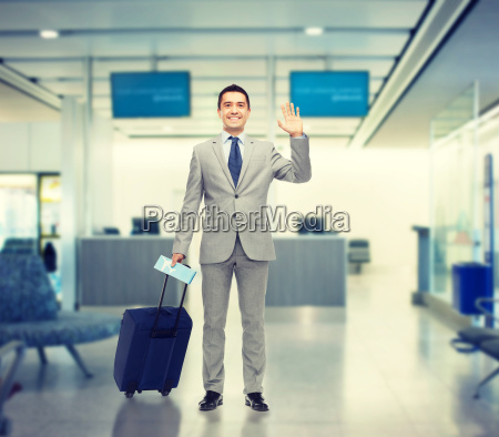 happy businessman in suit with travel