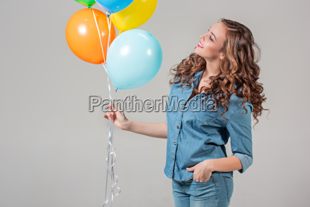 girl with bunch of colorful balloons