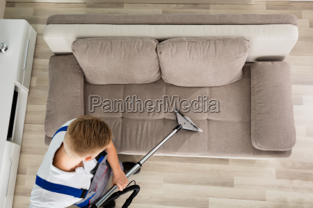 young man cleaner sofa with vacuum
