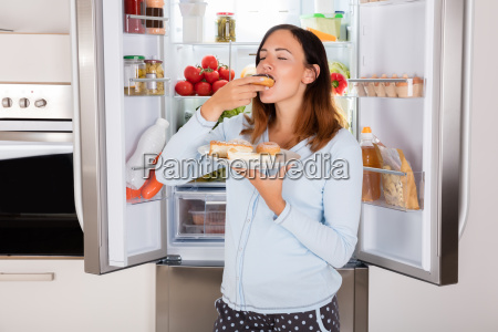 woman eating sweet food near refrigerator