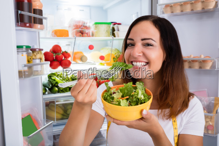 woman eating salad in front of