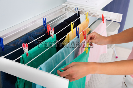 person hanging wet cloth on clothes