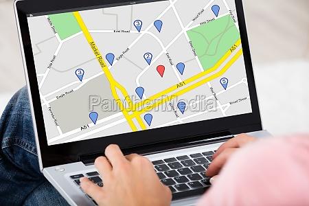 woman using gps map on laptop
