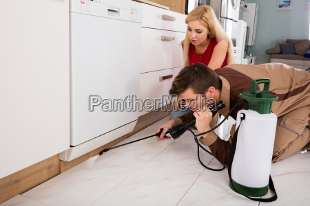 woman looking at male worker spraying