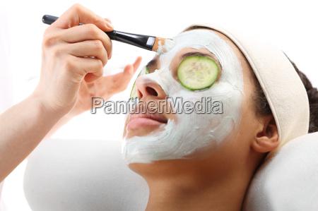a beautician applies a moisturizing mask