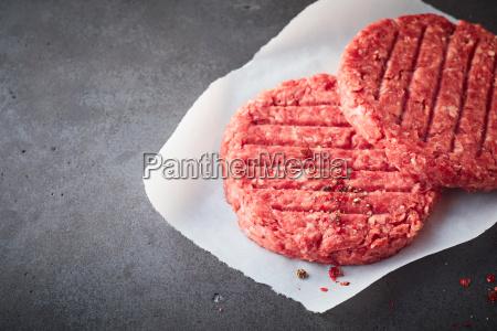 raw beef hamburger patties on wax