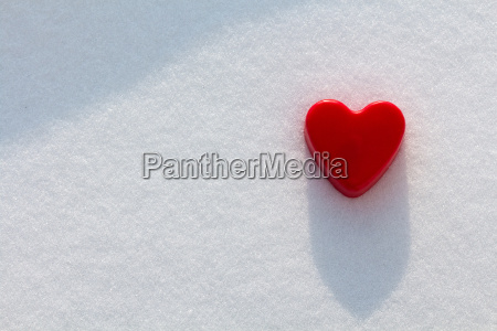 red heart in the snow with